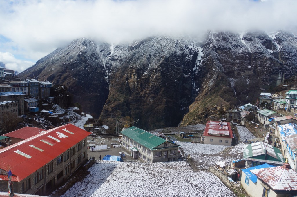Namche emerges from the clouds in the morning light, new snowfall on the rampart across the valley.