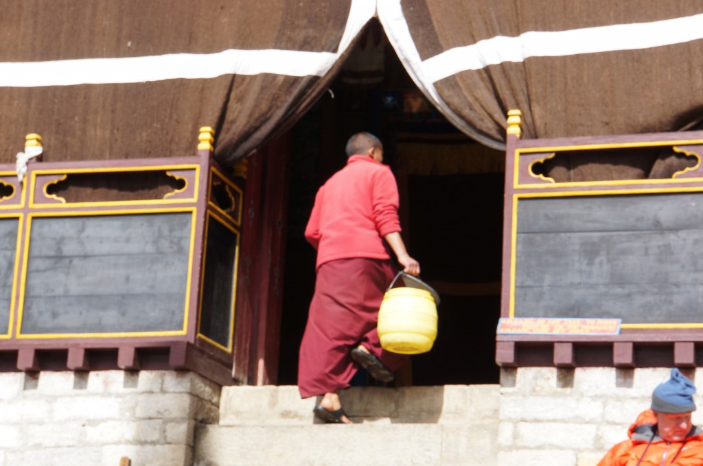 A monk enters the inner sanctum with water to clean the floor before we enter.
