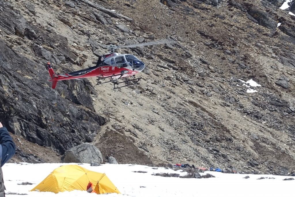 A chopper arrives to whisk one of our trekking buddies to lower elevations.  (Photo: Blake Penson)