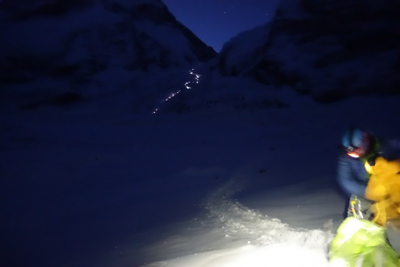 A string of headlamps shows the route above, while we get the 'pons on at crampon point.  (Photo: Blake Penson)