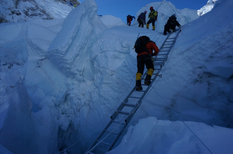 LC descends three ladders lashed together, crossing a deep dark crevasse.  (Photo: Justin Merle)