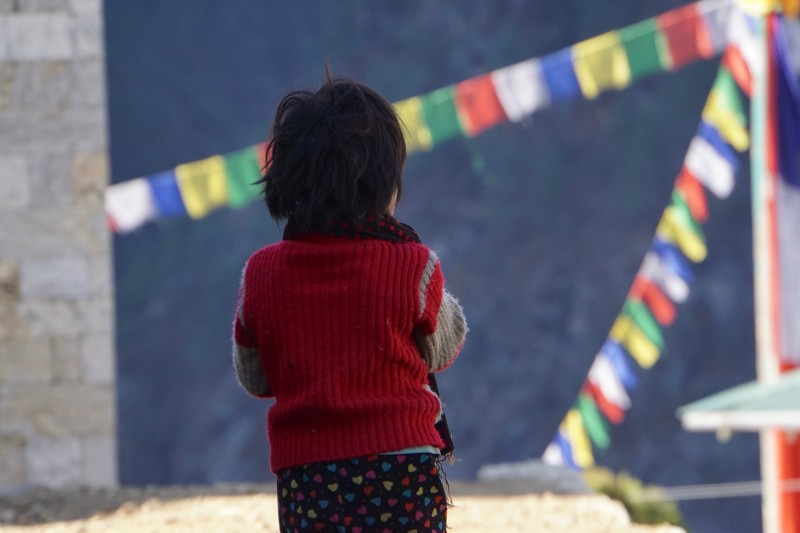 A girl watches the sunrise approach in Monjo.