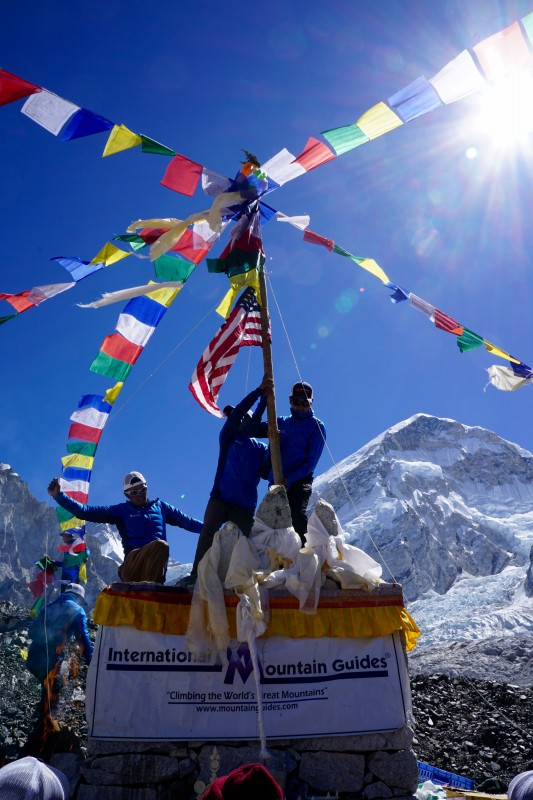It stands tall and mighty, adorned with flags. Prayer flags are then spread in five directions from this central pole.