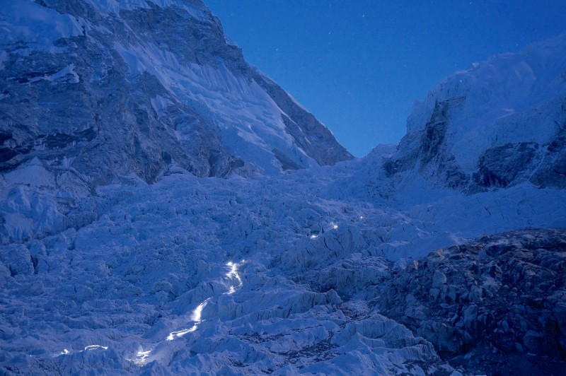 The icefall lit by moonlight... and by headlamps of retreating climbers. (Photo: Justin Merle)