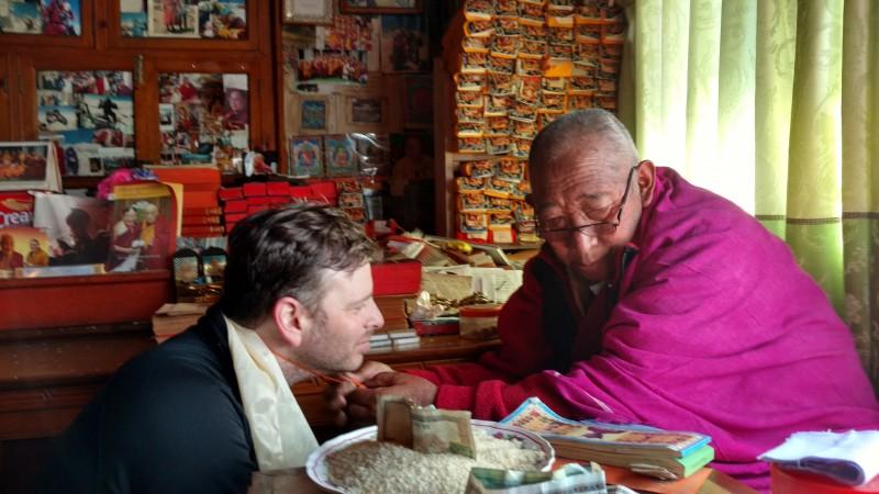 I receive a cord from Lama Geshi... it is tied next to the one he gave me last year. (Photo: Justin Merle)