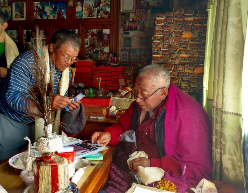 Lama Geshi inspects the photo of Gene and nods in approval.