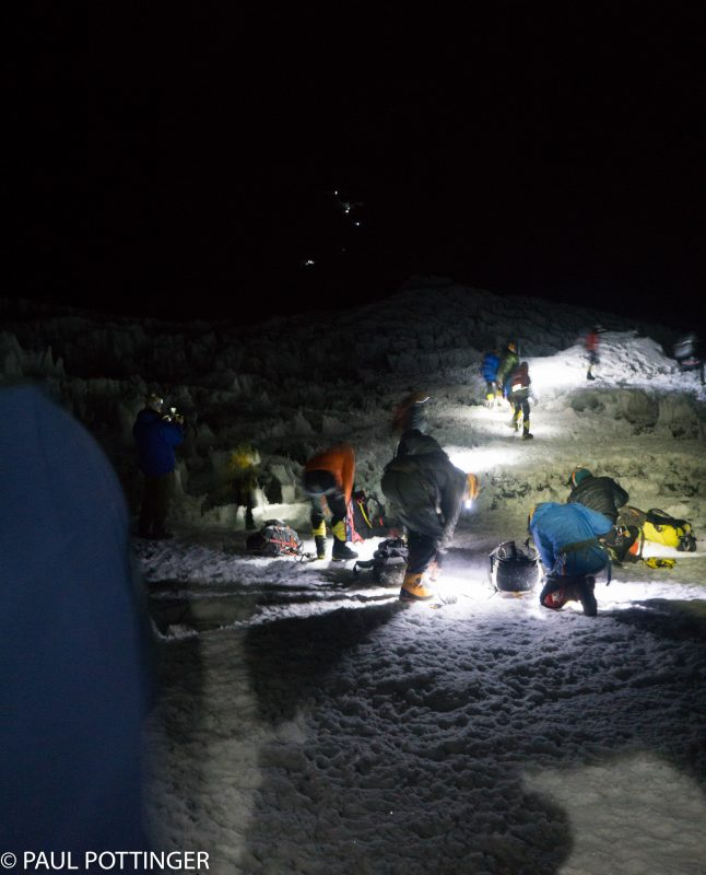 Getting the spikes on at Crampon Point. You can see the headlamps of a handful of climbers on the route above us. Looks busy today, because so many IMG climbers are headed up at once!