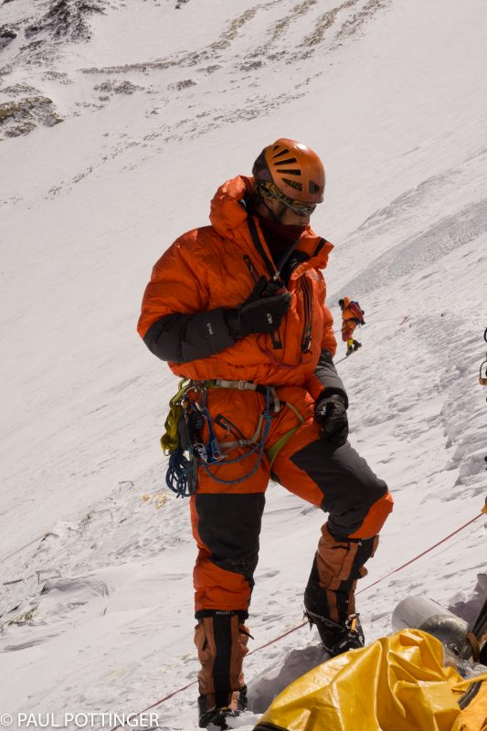Justin Merle at Camp 3, coordinating the climb via radio. A climber descends the face in the background.