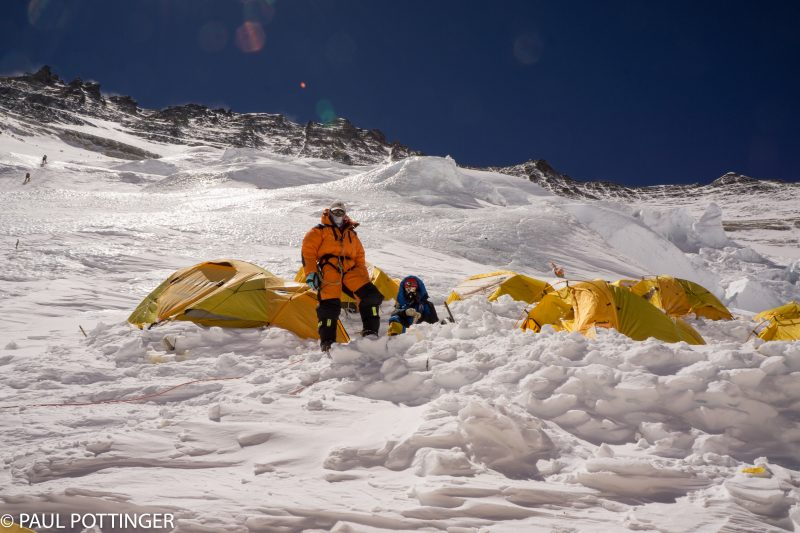 Ramin and his Sherpa guide look down from the middle row of tents at Upper Camp 3. Climbers on the route seen upper left.