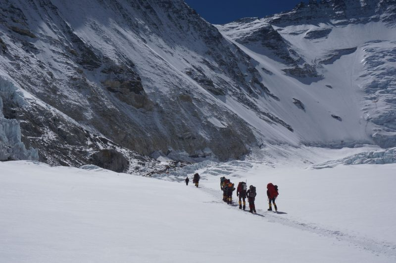 We move towards Camp 2, barely visible atop the pile of dark rocks at photo center. (Photo: Justin Merle)