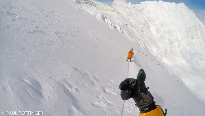 Giving a thumbs up to Nima Dorje soon after the dogleg leading to the Yellow Band. Our tents at Camp 3 barely visible near the bottom of the column of climbers. (GoPro Screenshot)