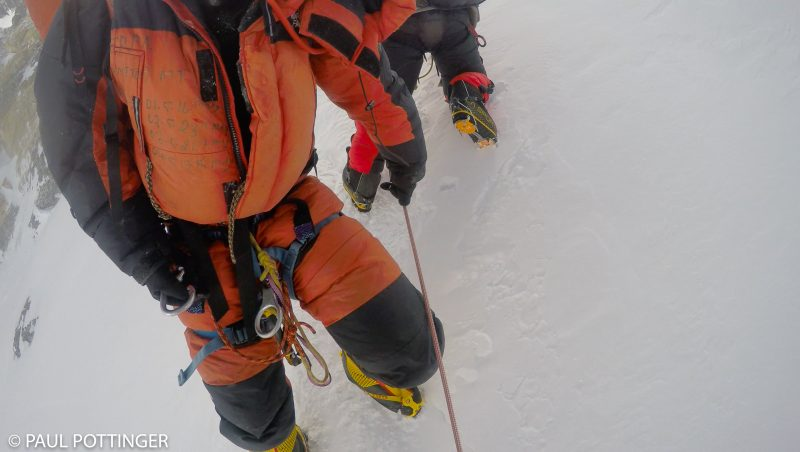 Another Sherpa climber descending the route. Many experienced Sherpa mountaineers are veterans of prior expeditions, which they wear with pride written on their down suits, as this man does. Four prior Everest summits are logged on his suit. (GoPro Screenshot)