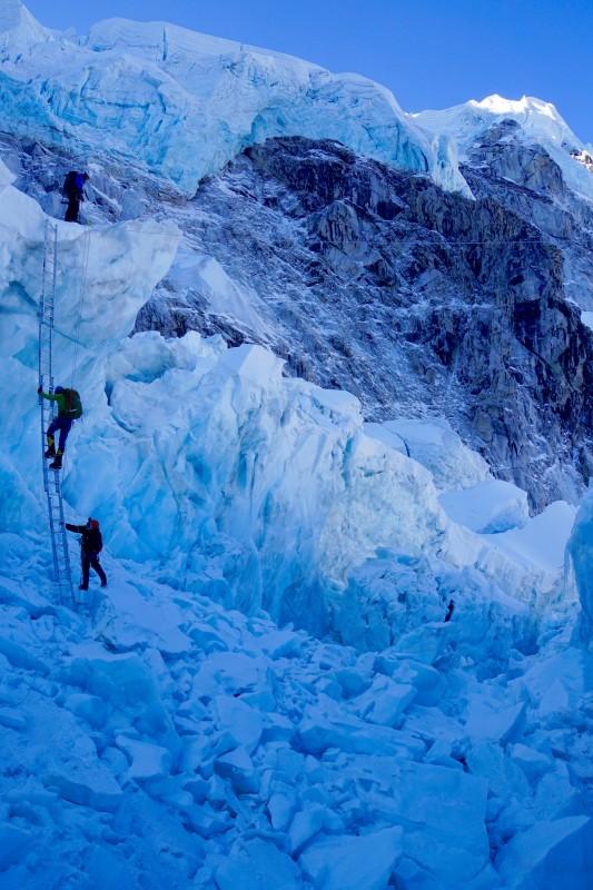 Siva making progress on the ladder... hanging glaciers of Nuptse above.